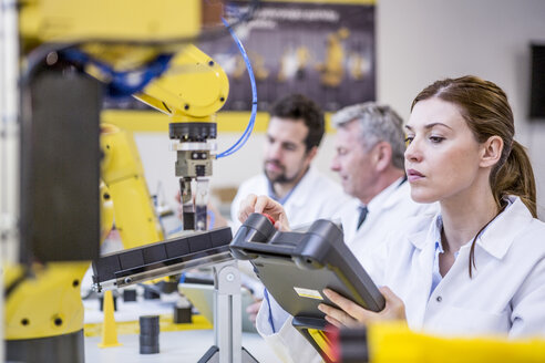 Engineers examining industrial robots - WESTF23411