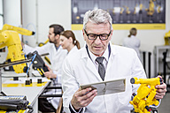 Engineer holding tablet and model of an industrial robot - WESTF23417