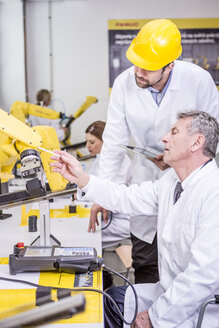 Two engineers examining industrial robot - WESTF23420