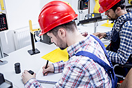 Man in factory wearing hard hat taking notes - WESTF23423
