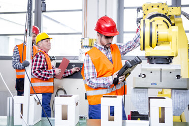 Three men in factory with industrial robot - WESTF23429
