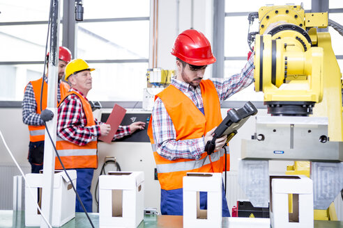 Three men in factory with industrial robot - WESTF23429