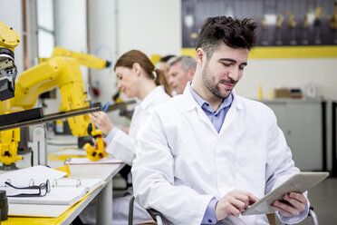 Engineer holding tablet with industrial robots in background - WESTF23435