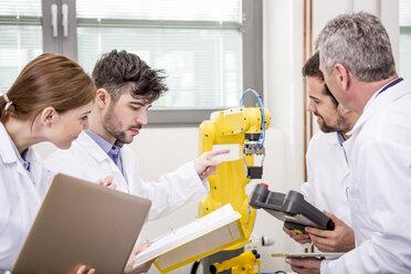 Engineers examining industrial robot - WESTF23441