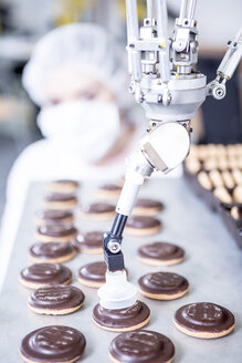 Robot handling cookies with woman in background - WESTF23450