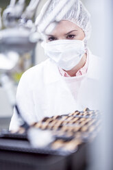 Woman in factory looking at robot handling cookies - WESTF23453