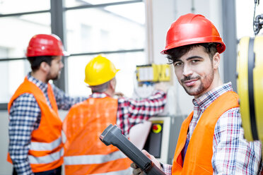 Portrait of confident man wearing hard hat in factory - WESTF23459