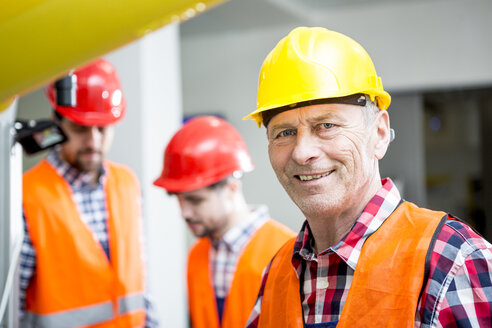 Portrait of smiling man wearing hard hat in factory - WESTF23462