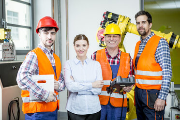 Portrait of confident staff in factory with industrial robot in background - WESTF23465
