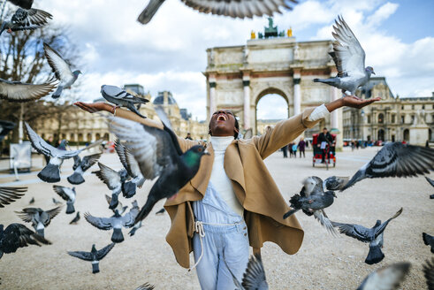 France, Paris,  Happy young woman with flying pidgeons at Arc de Triomphe - KIJF01548