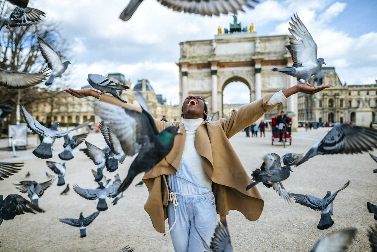 France, Paris,  Happy young woman with flying pidgeons at Arc de Triomphe - KIJF01548 - Kiko Jimenez/Westend61