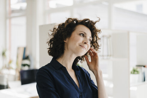 Businesswoman in office thinking and smiling - KNSF01547