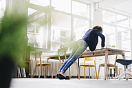 Businesswoman in office doing push ups on desk - KNSF01556