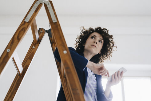 Businesswoman standing by ladder in office, holding smartphone - KNSF01559