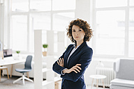 Businesswoman standing in her office with arms crossed - KNSF01568