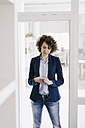 Businesswoman standing in office door, using smartphone - KNSF01577