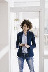 Businesswoman standing in office door, using smartphone - KNSF01577