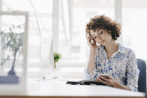 Businesswoman in office with smartphone and diary, looking worried - KNSF01583