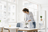 Businesswoman in office taking care of bonsai tree - KNSF01586