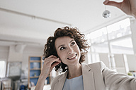 Businesswoman in office holding disco balls on her ears - KNSF01610