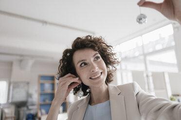 Businesswoman in office holding disco balls on her ears - KNSF01610