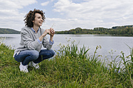 Woman crouching at lakeshore, smelling grass blade - KNSF01619