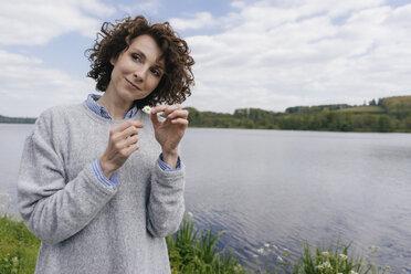 Woman at lake plucking daisy's petals - KNSF01622