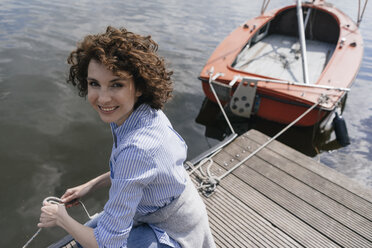 Woman standing on jetty with moored sailing boat - KNSF01625