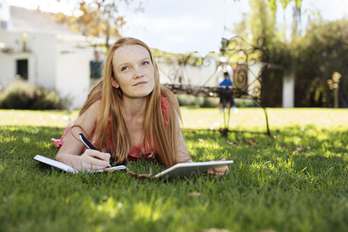 Grl with long red hair lying in grass with tablet and notebook - ZEF13931