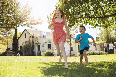 Brother chasing sister in garden - ZEF13934