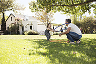 Father playing with daughter in grass - ZEF13937