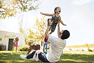 Father playing with daughter in garden - ZEF13940