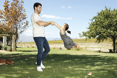 Father playing with daughter in garden - ZEF13946