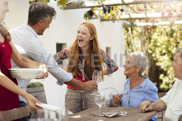 Happy family setting table outside for lunch - ZEF13964