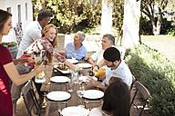Happy family preparing lunch on garden table - ZEF13967
