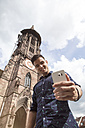 Germany, Freiburg, young man taking a selfie at the minster - MIDF00842