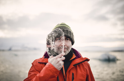 Iceland, man with a piece of ice covering half of his face - RAEF01883