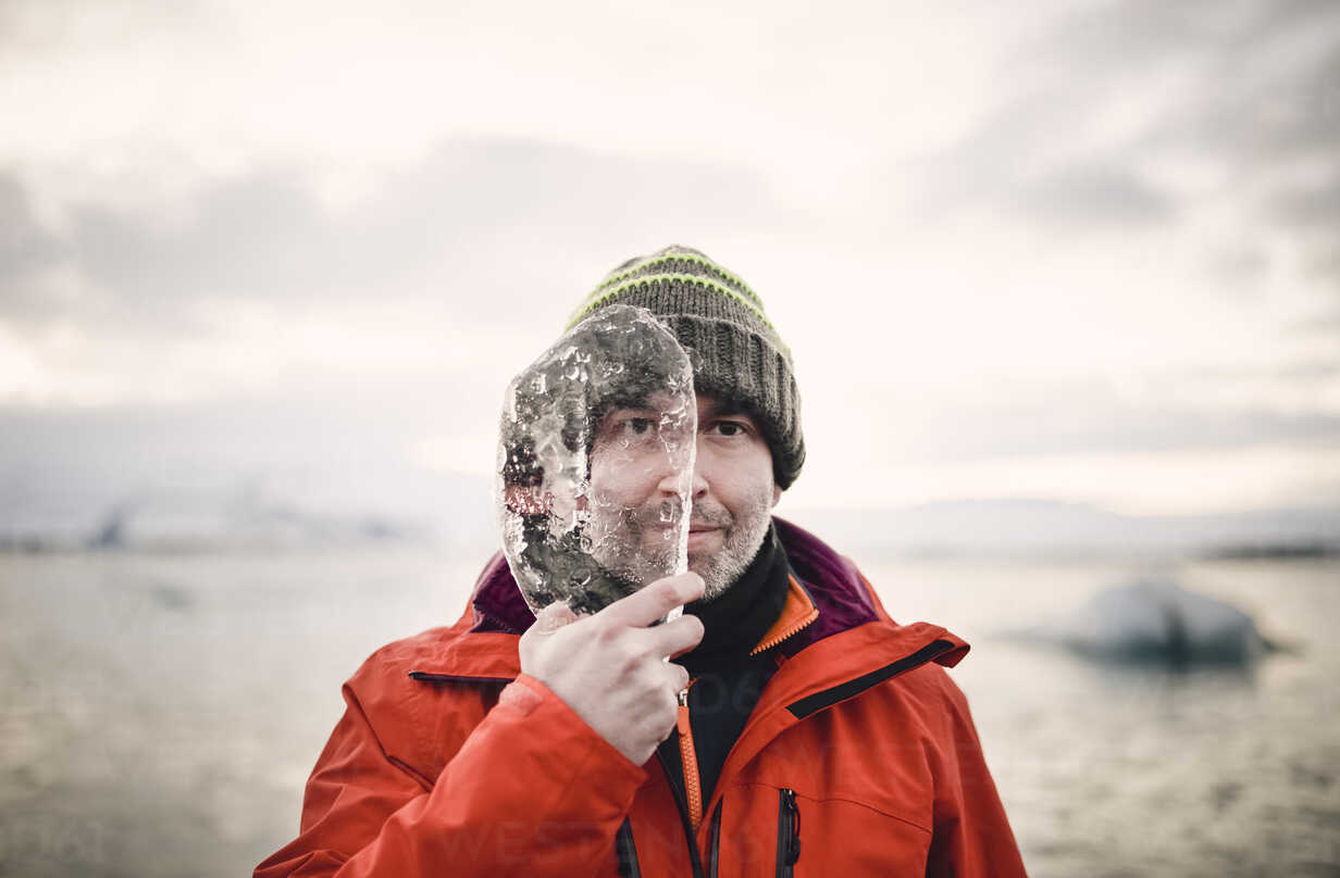 Iceland, man with a piece of ice covering half of his face - RAEF01883 - Ramon Espelt/Westend61
