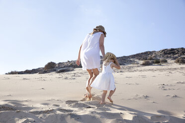 Spain, Fuerteventura, mother walking with daughter on the beach - MFRF00858