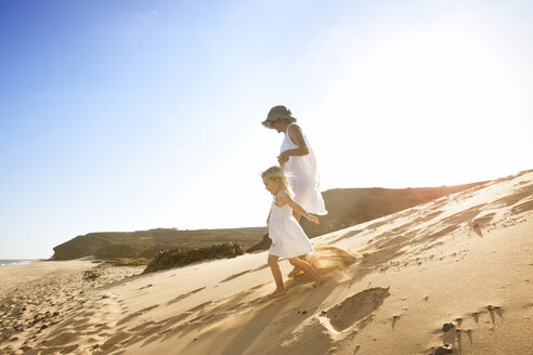 Spain, Fuerteventura, mother running with daughter on the beach - MFRF00861