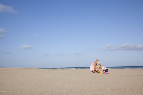 Spain, Fuerteventura, mother and daughter playing on the beach - MFRF00870