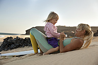 Spain, Fuerteventura, happy mother and daughter on the beach next to surfboard at sunset - MFRF00873
