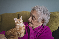Senior woman sitting with tabby cat on the couch - RAEF01884
