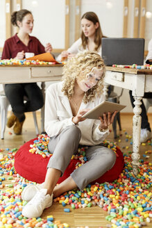 Woman using tablet in office surrounded by colorful polystyrene parts - PESF00633