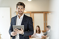 Portrait of confident businessman holding tablet with a meeting in background - PESF00642