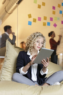 Woman in office using tablet in bean bag with meeting in background - PESF00681