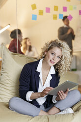Portrait of woman in office using tablet in bean bag with meeting in background - PESF00684