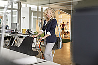 Portrait of woman with bicycle in office - PESF00687
