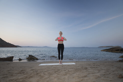 Greece, Crete, woman practicing yoga on the beach - CHPF00404