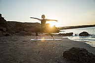 Greece, Crete, woman practicing yoga on the beach at sunset - CHPF00407